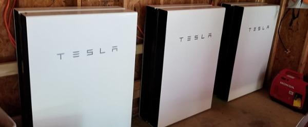 Stack of six tesla Powerwalls installed in a garage